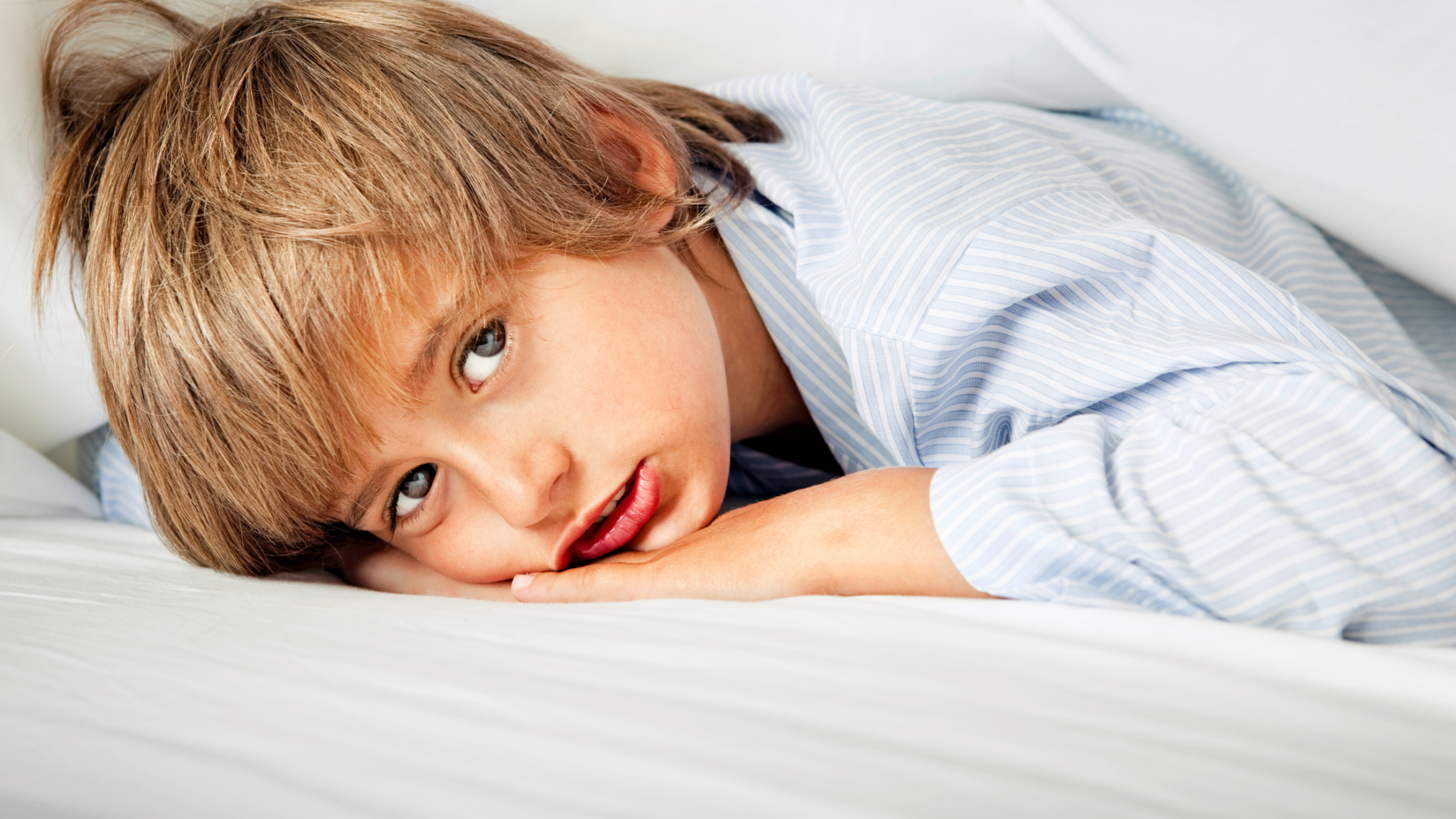 A child with ADHD, lying in bed but struggling to fall asleep.